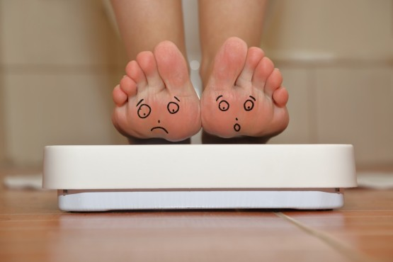 bigstock-Feet-on-bathroom-scale-with-ha-83218232-1024x683