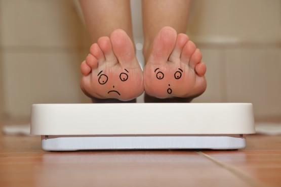 bigstock-Feet-on-bathroom-scale-with-ha-83218232-1024x683